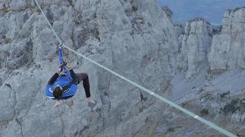 un homme essaie de s'équilibrer en slackline sur une corde raide dans les montagnes. video