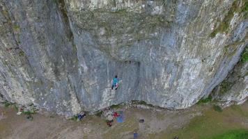 um homem cai e é salvo por sua corda enquanto escala uma montanha. video