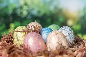 On a blurred green background, a natural nest with moss and painted Easter eggs. Selective focus photo