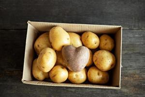 papa roja en forma de corazón en una caja de cartón entre papas blancas. foto