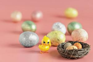 Easter eggs in a natural nest with bird eggs. Painted eggs and a decorative chicken on a pink background of pastel colors. Selective focus photo