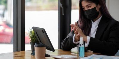 Joven empresaria con mascarilla mientras trabaja en una computadora en la oficina foto