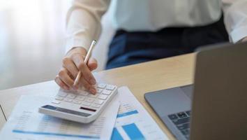 Mujer calculando el impuesto sobre la renta individual del documento financiero durante la nota de algunos datos para pegar en el cristal de la ventana con la calculadora. foto