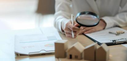Hand holding magnifying glass and looking at house model, house selection, real estate concept. photo