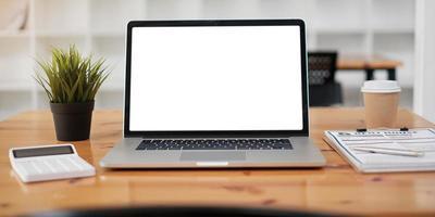Captura recortada del lugar de trabajo con pantalla en blanco de tableta y suministros de oficina en un espacio de trabajo simple foto