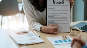 venta contrato de compra para comprar una casa, el agente de bienes raíces presenta el préstamo hipotecario y le da las llaves al cliente después de firmar el contrato para comprar la casa con el formulario de solicitud de propiedad aprobado foto