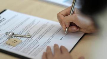 Vista cercana de las manos del empresario que firma los documentos de la casa de arrendamiento y tiene las llaves del apartamento en el papeleo. foto