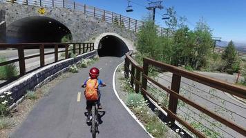 um menino anda de bicicleta por um túnel em uma trilha pavimentada na floresta. video