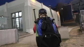 A boy walking home after baseball practice. video