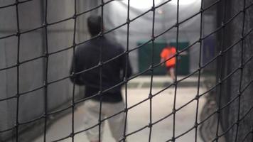 un entraîneur de baseball lance dans les cages des frappeurs. video