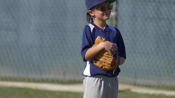 A boy in the outfield playing in a little league baseball game. video