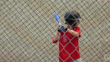 un garçon pratique le baseball dans les cages des frappeurs. video