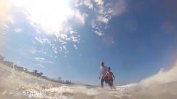 POV view of a boy and his father body boarding in the waves at the beach. video