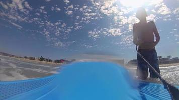 POV view of a boy body boarding in the waves at the beach. video