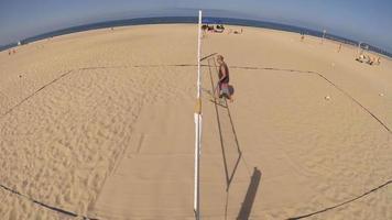 A man rakes a beach volleyball court. video