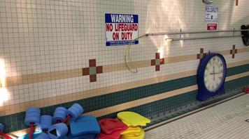 Equipment and signs around an indoor pool area. video