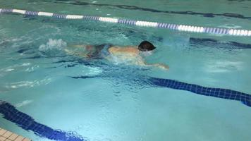 A boy swims freestyle during swimming lessons in a pool. video