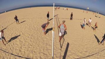 POV of senior men playing beach volleyball. video