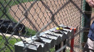 battes dans un rack à un petit match de baseball de ligue. video