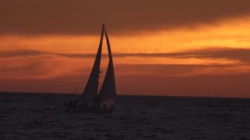 de zon gaat onder over een zeilboot bij zonsondergang. video