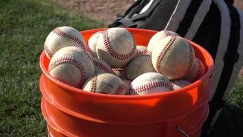 un balde de pelotas un juego de béisbol de la liga pequeña. video