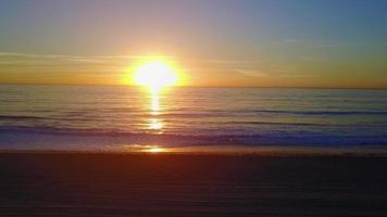 Aerial drone uav view of a sunset over the beach and ocean. video