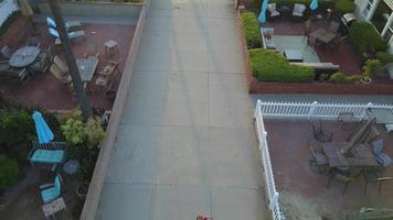 drone aéreo uav vista de um menino jogando futebol futebol em uma rua para pedestres em um bairro. video