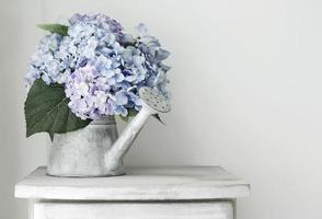Hydrangea flowers in grunge zinc watering can on vintage wooden cabinet photo