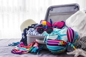 Colorful bikini and clothes in luggage on the bed photo
