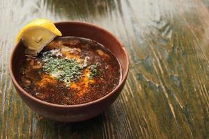 tomato soup solyanka with slice of lemon in clay bowl photo