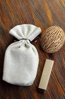 small fiber pouch for present on wooden table with chocolate and  nut shell decoration photo