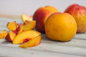 Whole peaches and slices, on white wooden board photo