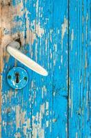 Detalle de la antigua puerta de madera verde azulado y manija de puerta de metal foto