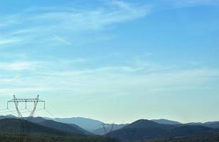 Línea de energía eléctrica y pilones contra el paisaje de montaña foto
