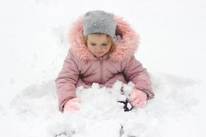Little girl is sitting in the snow, playing with fresh snow that fell over night photo