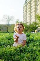 Linda niña enviando un beso, sentada en la hierba, en un día soleado de primavera foto