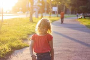 Little girl making faces and having fun on beautiful summer sunset photo