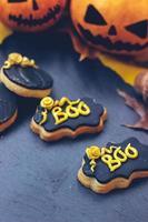 Galletas de jengibre de halloween sobre fondo oscuro, con mini calabazas de halloween y decoración foto
