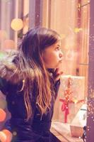 Beautiful little girl in front of confectionery shop, decorated with wrapped gift boxes and candies. Christmas concept, window shopping photo