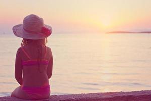 niña sentada en la playa, mirando el atardecer foto