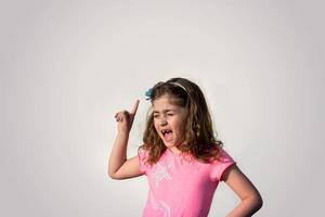 Little girl screaming and pointing her finger against gray background photo