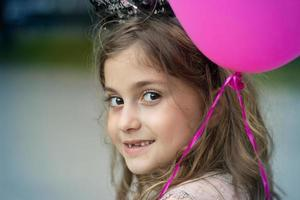 Portrait of a beautiful little smiling girl with pink balloon with copy space photo