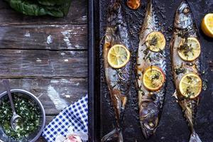 Three grilled fish, on black baking tray, with copy space photo