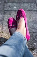 piernas de mujer en mocasines rosas, sentado relajado foto