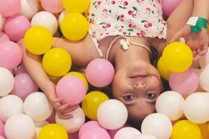 Hermosa niña en el patio de recreo lleno de bolas de colores, con espacio de copia foto