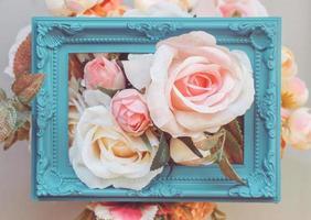 composición hecha de marco de fotos y flores artificiales en colores pastel