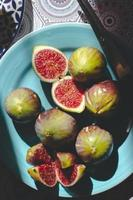 Higos maduros enteros y medio cortados sobre fondo de fruta de placa azul foto