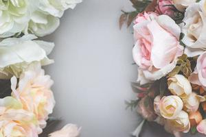 Bouquet of artificial pastel color flowers on gray background, top view with copy space photo