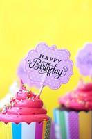 deliciosos cupcakes de fresa con tarjeta de felicitación de cumpleaños feliz sobre fondo amarillo. fondo de fiesta foto