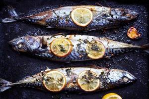 Baked fresh mackerel fish, with lemon and seasoning,  on baking tray photo